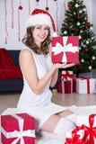 Hübsche Frau in Sankt-Hut, der nahe Weihnachtsbaum mit Geschenken sitzt Lizenzfreie Stockfotos
