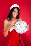 Hübsche Frau in Santa Claus Costume Showing Clock Stockbild