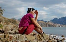 Hübsche Frau sitzt auf der Küste und schaut fern Stockbild