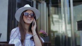Hübsche Frau sitzt auf Straße in umsponnenem Holzstuhl stock video
