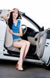 Hübsche Frau sitzt im Auto mit der geöffneten Tür Lizenzfreies Stockfoto