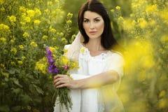 Hübsche Frau sitzt mit Blumenstrauß von Wildflowers auf dem gelben Gebiet in den Sonnenunterganglichtern, Sommerzeit Lizenzfreies Stockbild
