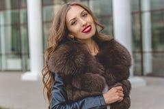Hübsche Frau trägt dunklen Pelzluxusmantel lizenzfreies stockbild
