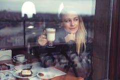 Hübsche Frau trinkender Latte lizenzfreie stockfotos