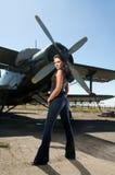 Hübsche Frau und ein Flugzeug stockfotografie