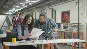 Hübsche Frau und hübscher bärtiger Mann im Büro in Verbindung stehen, lachend Beardie, das emotional Informationen bespricht stock video footage