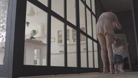 Hübsche Frau und ihre Babystellung auf dem Boden zu Hause Das Kind, das ersten Schritt, Mutter sie stützen lässt Mutterspiele stock footage