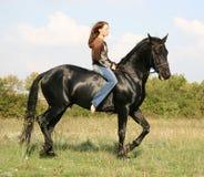 Hübsche Frau und schwarzes Pferd Stockbild