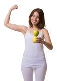 Hübsche Frau zeigt Stärke, wenn Sie Äpfel essen lizenzfreies stockbild