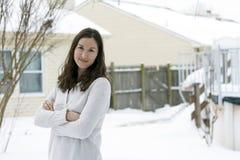 Hübsche Frauenüberfahrtarme im Schnee Stockfoto