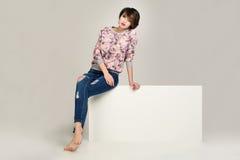 Hübsche Frauen in der Jacke mit Blumen und Blue Jeans mit Löchern Lizenzfreie Stockbilder