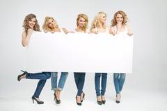 Hübsche Frauen, die leeres Brett halten Lizenzfreies Stockfoto