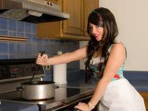 Hübsche Frauen-rührender Potenziometer auf Ofen Lizenzfreie Stockfotografie