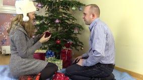 Hübsche Frauenaustausch Weihnachtsgeschenke stellt sich mit ihrem Ehemann dar stock video footage