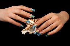 Hübsche Frauenhand mit perfekten gemalten Nägeln auf schwarzem Hintergrund Stockfotografie