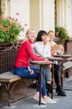 Hübsche Frauenterrasse der Gruppe mit dem Ablesen und dem Hören sich unterhalten Kaffeecaf? Weise sich zu entspannen und neuzulad stockfotos