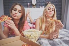Hübsche Freunde, die ungesundes Lebensmittel essen stockfotos