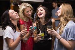 Hübsche Freunde, die zusammen etwas trinken Stockbild