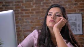Hübsche gebohrte Frau seufzt nahe Laptop mit dem ruhigen Gesicht, ruhig und überzeugt und liegt auf der Tabelle, Innen, Ziegelste stock footage