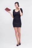 Hübsche Geschäftsdame, die mit Buch steht Stockfotografie