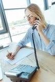 Hübsche Geschäftsfrau, die Anmerkungen bei der Unterhaltung am Telefon macht Stockfotos