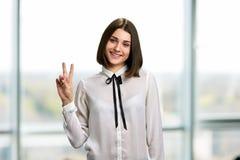 Hübsche Geschäftsfrau, die Frieden gestikuliert stockfoto