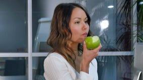 Hübsche Geschäftsfrau, die grünen Apfel im Büro isst stock footage