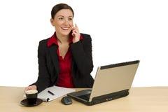 Hübsche Geschäftsfrau, die hinter Schreibtisch benennt Lizenzfreies Stockfoto