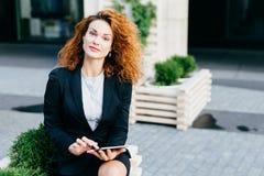 Hübsche Geschäftsfrau mit dem gelockten Haar, reine Haut- und Rotlippen, tragendes formales Kostüm, beim Sitzen Café am im Freien stockfotos