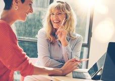Hübsche Geschäftsfrau zwei bei der Vorstellungsgesprächsitzung am modernen Büroplatz horizontal Unscharfer Hintergrund Stockfoto