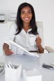 Hübsche Geschäftsfraulesezeitung an ihrem Schreibtisch Stockbild
