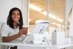 Hübsche Geschäftsfraulesezeitung an ihrem Schreibtisch Stockfotos