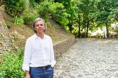 Hübsche grüne Augen entspannten sich Mann nahe mittelalterlichen Wänden Stockfotografie
