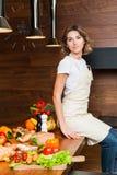 Hübsche Hausfrau in der Küche, die auf Tabelle sitzt Lizenzfreie Stockfotos