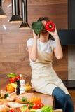 Hübsche Hausfrau in der Küche, die auf Tabelle sitzt Stockbilder