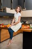Hübsche Hausfrau in der Küche, die auf Tabelle sitzt Lizenzfreie Stockbilder