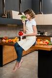 Hübsche Hausfrau in der Küche, die auf Tabelle sitzt Stockfoto