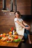 Hübsche Hausfrau in der Küche, die auf Tabelle sitzt Stockfotografie
