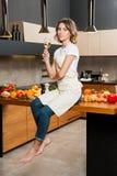 Hübsche Hausfrau in der Küche, die auf Tabelle sitzt Stockbild