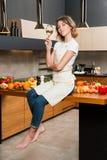 Hübsche Hausfrau in der Küche, die auf Tabelle sitzt Lizenzfreies Stockbild