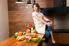 Hübsche Hausfrau in der Küche, die auf Tabelle sitzt Lizenzfreie Stockfotografie