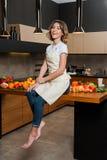 Hübsche Hausfrau in der Küche, die voll auf Tabelle mit Lebensmittel sitzt Lizenzfreie Stockbilder
