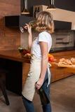 Hübsche Hausfrau in der Küche mit Glas Wein Lizenzfreie Stockbilder