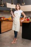 Hübsche Hausfrau in der Küche mit Glas Wein Stockfotografie