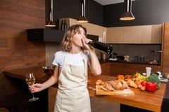 Hübsche Hausfrau in der Küche mit Glas Wein Stockbilder