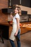 Hübsche Hausfrau in der Küche mit Glas Wein Stockfoto