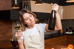 Hübsche Hausfrau in der Küche mit Glas Wein Lizenzfreies Stockbild