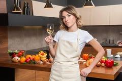 Hübsche Hausfrau in der Küche mit Glas Wein Stockfotos