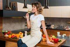 Hübsche Hausfrau in der Küche mit Glas Wein Lizenzfreie Stockfotos