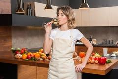 Hübsche Hausfrau in der Küche mit Glas Wein Stockbild